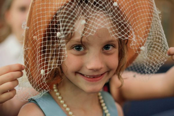 Girl Smiling wearing fun hat with veil and pearls, dressed up for Halloween