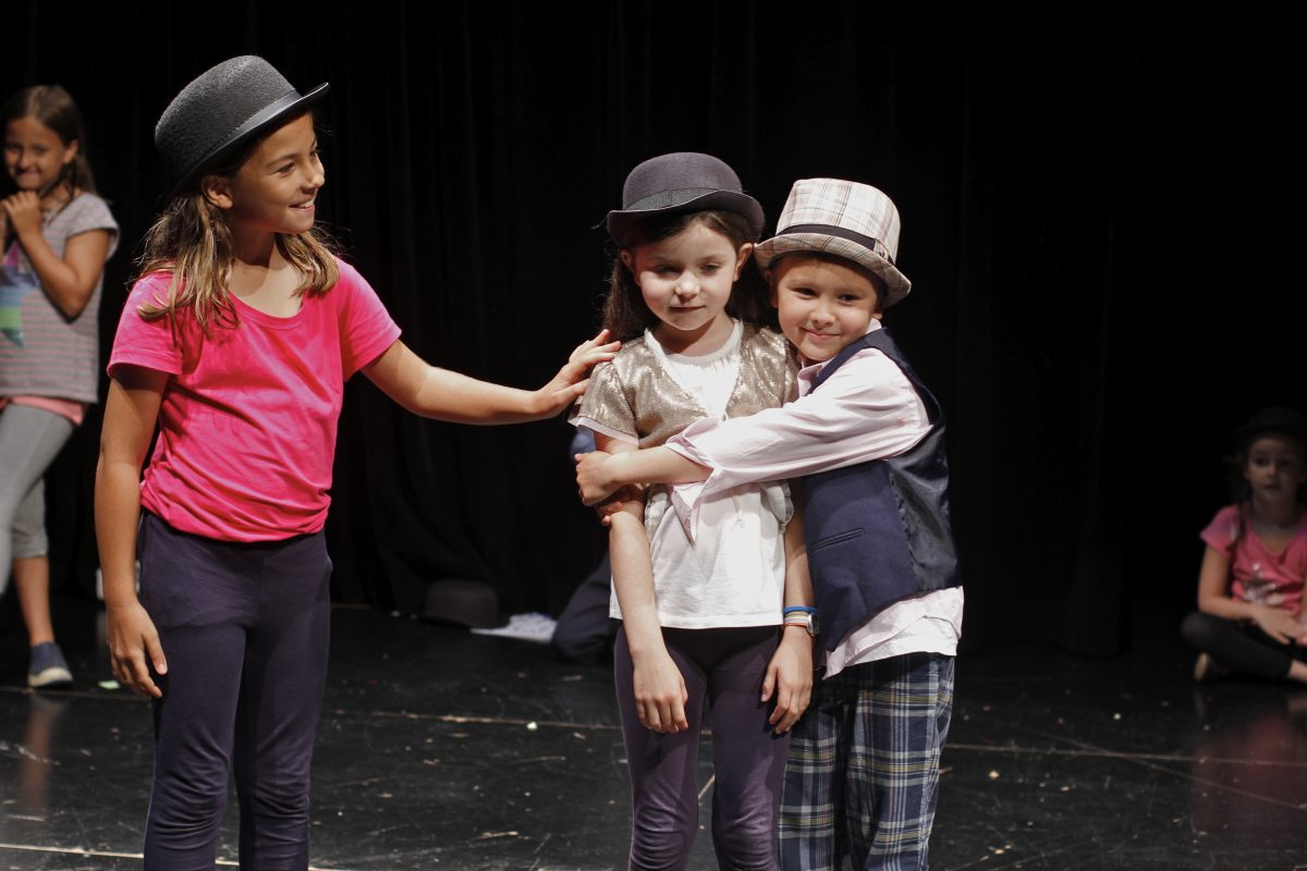 Group of kids acting on stage, wearing hats, showing empathy