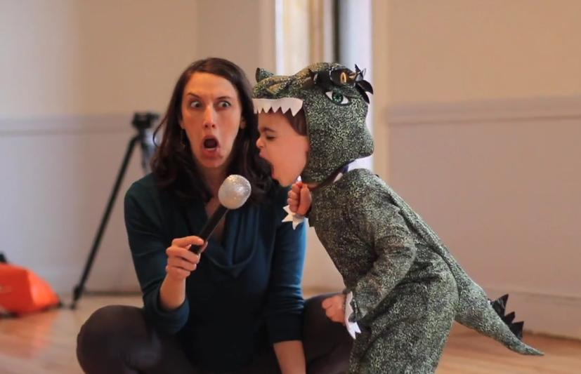 Jocelyn sitting on floor holding microphone for small boy dressed as a dinosaur roaring into the mic