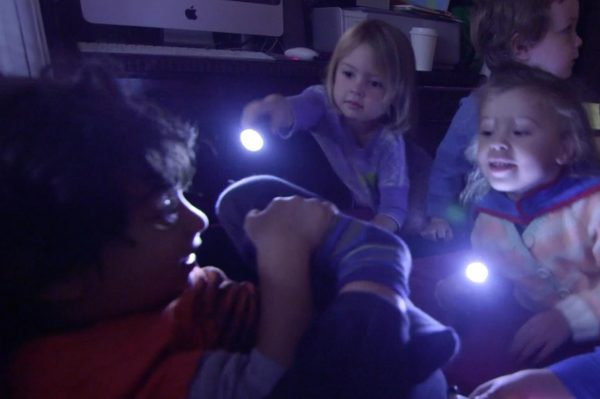 Group of kids playing in the dark with flashlights