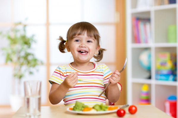 happy kid girl eating vegetables