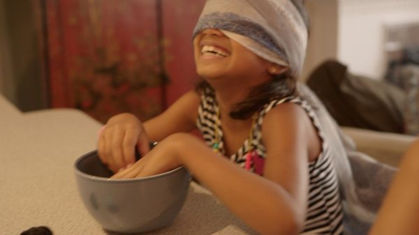 Girl smiling and guessing what's in a bowl with her hands while blindfolded - game
