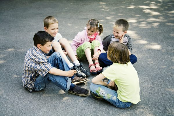 children sitting in a circle playing outside