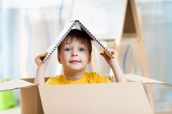 Boy popping head out of box with toy roof on head