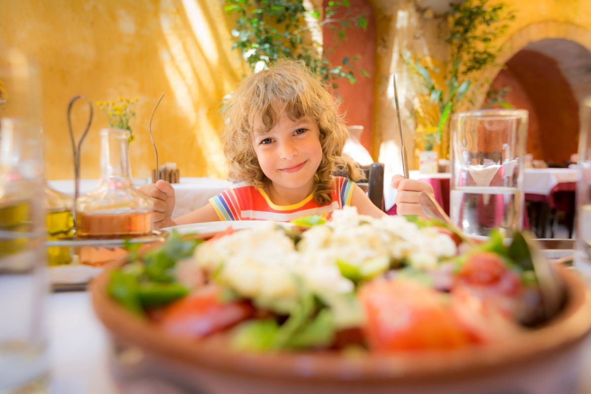 child eating in summer cafe outdoors