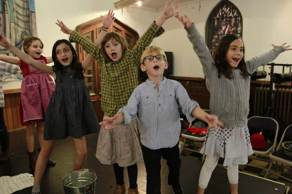 older kids singing and playing with arms stretched up