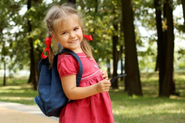 beautiful little girl with backpack walking in the park ready back to school
