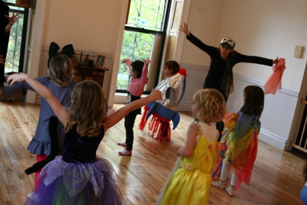 Teacher playing with kids dressed in costume, expressive movements with arms