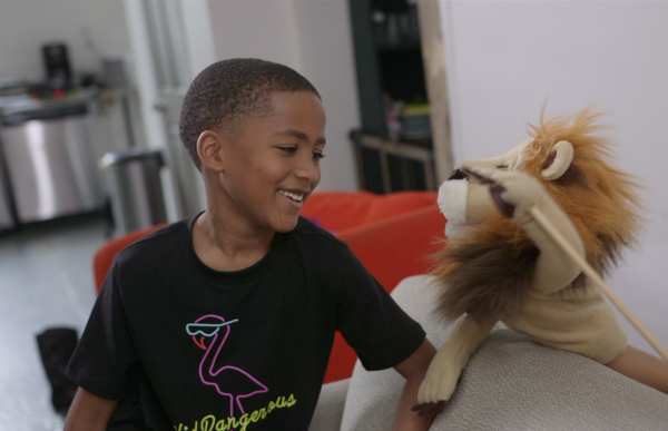 Boy smiling and sitting with lion puppet
