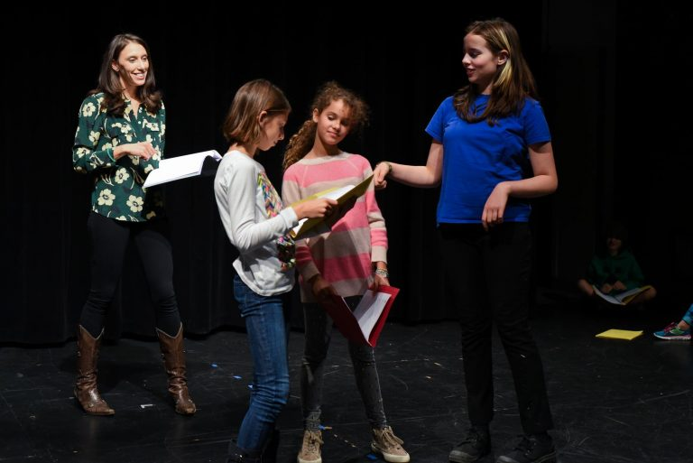 Jocelyn working with kids on stage on theater