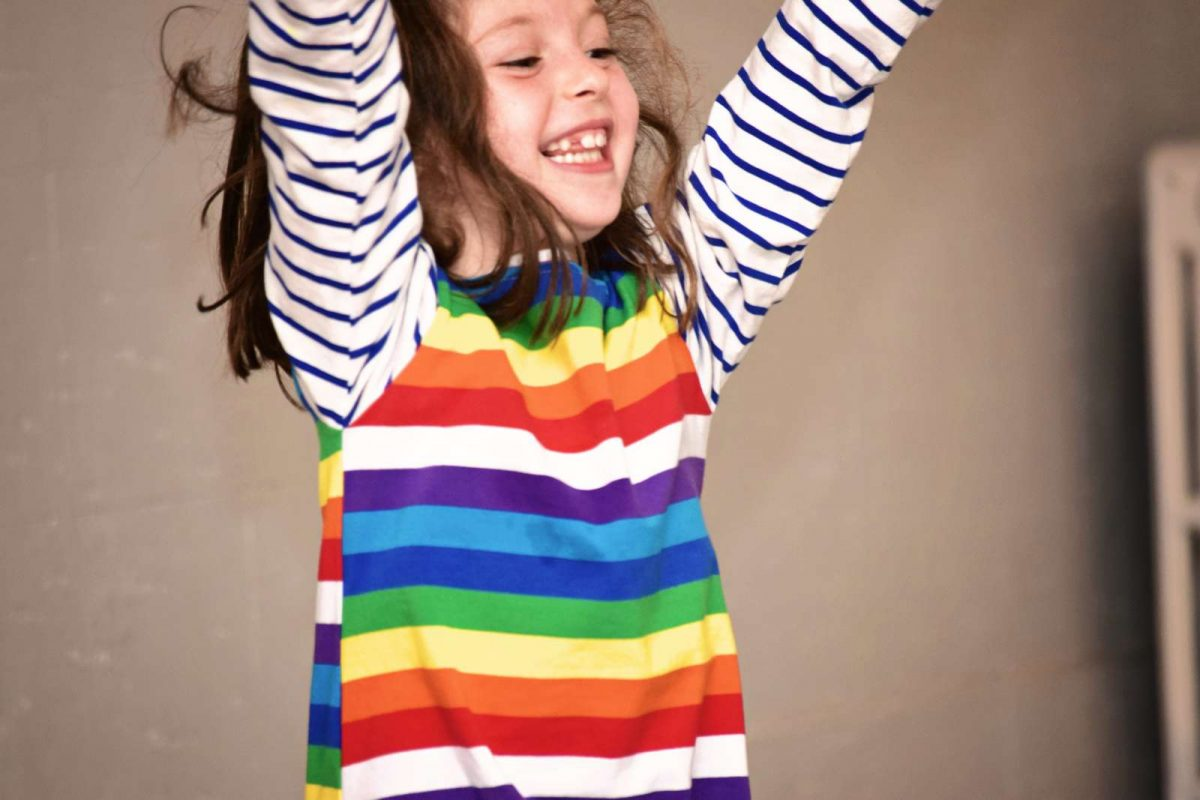 Girl in rainbow striped shirt smiling with arms up in the air