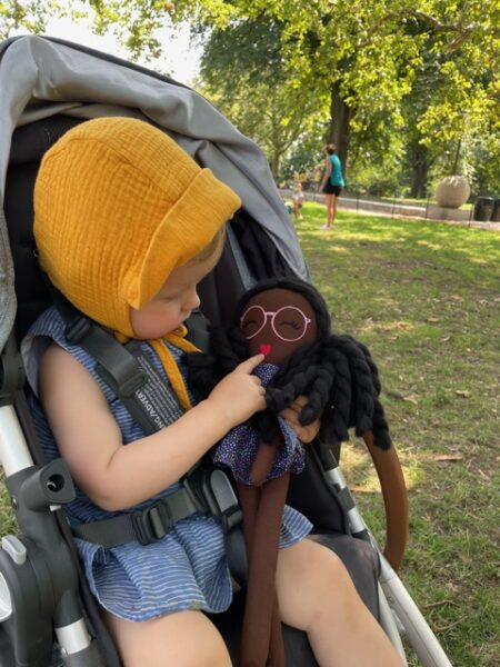 baby in stroller looking at modern doll