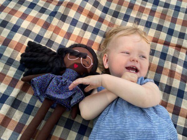 smiling baby on blanket holding modern doll black baby