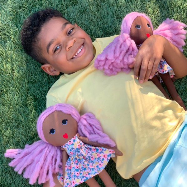 smiling black boy with two modern dolls with pink hair